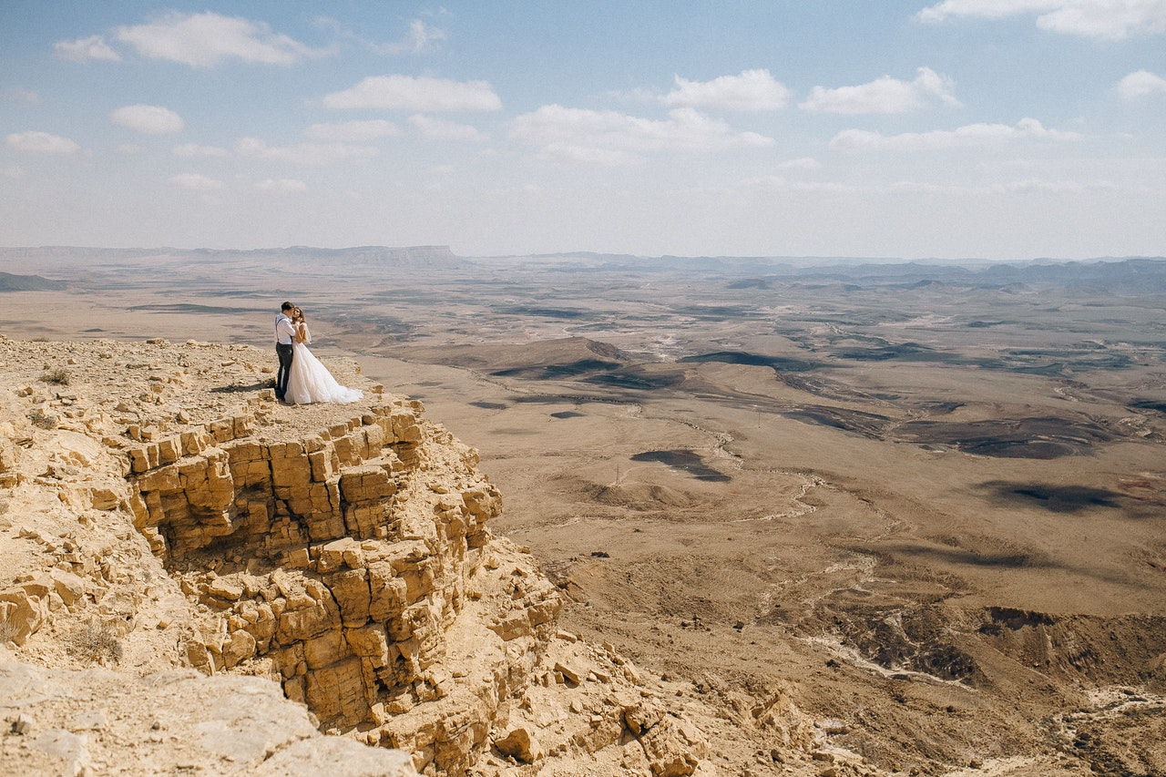 couple-standing-on-brown-rock-formation-4693193